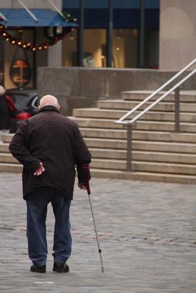 קשיש מחזיק את הגב עם מקל הליכה